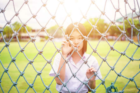 Cute portrait of innocent Asian girl teen student stand behind the rope net looking camera with sunshine