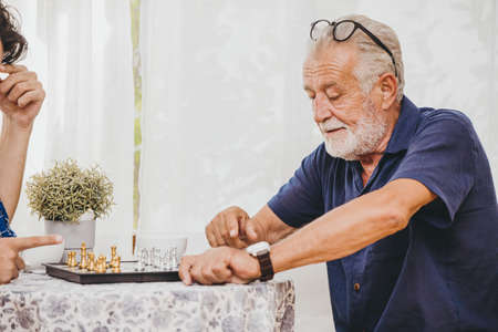 Old man playing Chess board game at home for training brain memory and thinking.