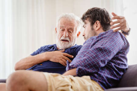 Differences of two generations male elder father with younger man son serious talking consulting together or telling history story at home.