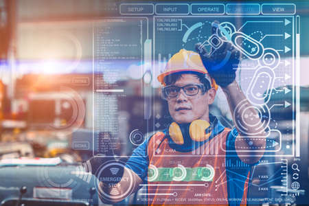 Smart engineer worker using advance technology visual holographic air screen to program and control robotic arm for automated production in modern future factory. Imagens