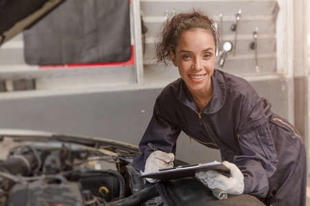 Portrait happy worker African American woman work for auto mechanic in garage checking car engine.