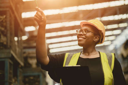 Black African professional women worker happy working count checking inventory production stock control in business factory industry warehouse waring engineer suit and helmet for safety Archivio Fotografico