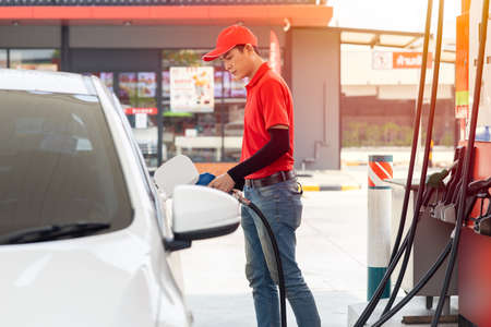 Gas station male man worker staff happy service working refill car gasoline fuel to traveler cars