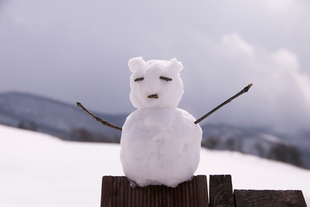 arms wide open: Little snowman with arms wide open at the top wooden structures