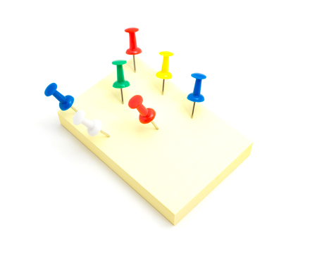 Seven push pins and yellow sticky note on isolated white background Stock Photo