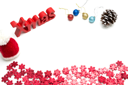 X-mas text and  pine cone, ball, fur hat, red snow flower decoration on white background