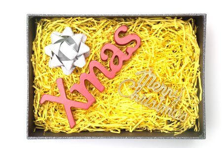 X-mas and merry christmas text, ribbon in black gift box with yellow packaging material