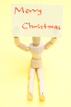 Joint dolls holding yellow notes with Merry Christmas