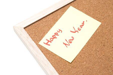 Happy new year writen on yellow sheet, cork board