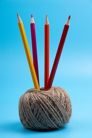 color pencils and string basket on blue background