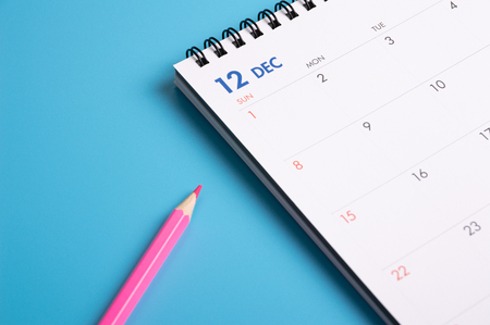 red pencil and calendar on blue background