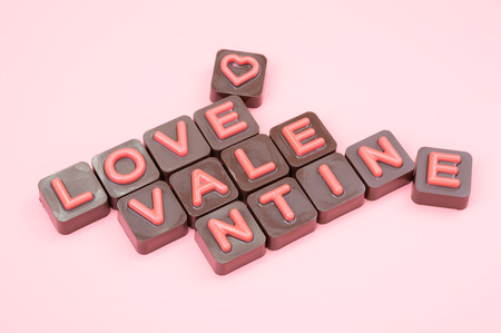 Valentine engraved in chocolate on colored background