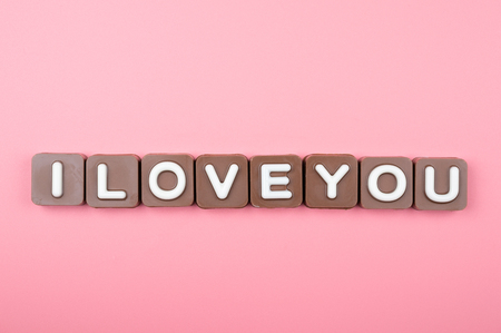 I love you engraved in chocolate on colored background Standard-Bild