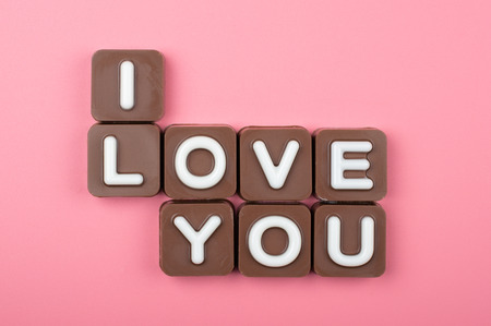 I love you engraved in chocolate on colored background Stock Photo
