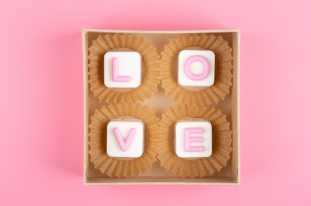 Love engraved in chocolate on colored background Stock Photo