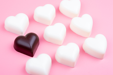 white and black heart chocolate on colored background
