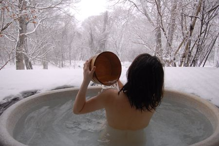 hot tub: young woman in hot spring with snowflake falling in Beijing Stock Photo