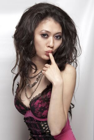 Sexy Asian female wearing lingerie and licking her finger photo