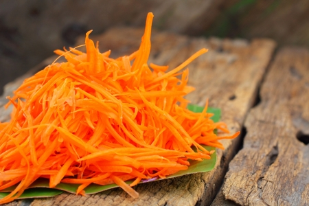 Grated carrot on a wooden plate