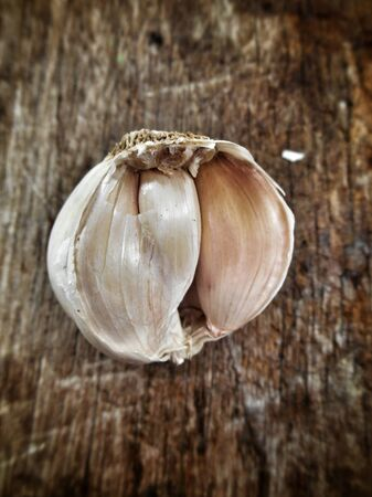 Garlic on the brown wood background photo