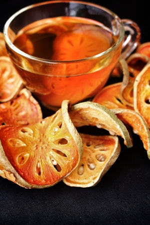 Slices of dried bael fruit and tea photo