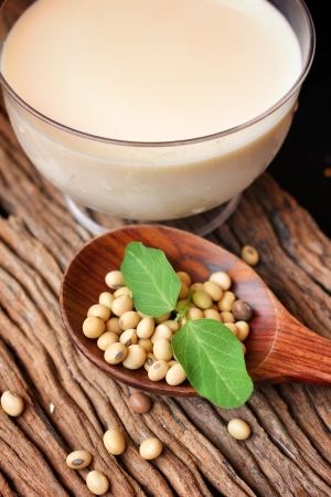 Soy milk with beans on wood background