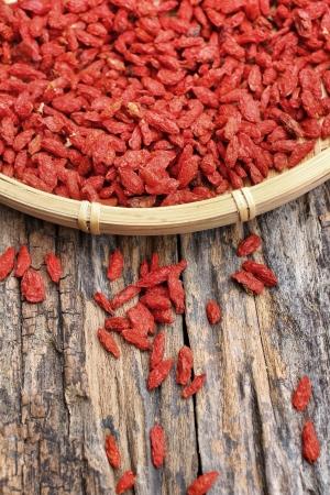 Red dried goji berries on wood background photo