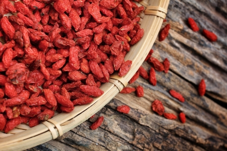 Red dried goji berries on wood background