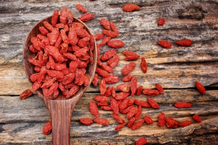 Red dried goji berries on wood background