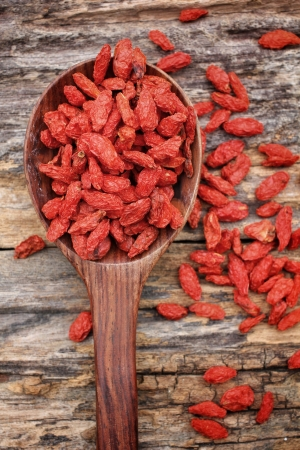 Red dried goji berries on wood background photo