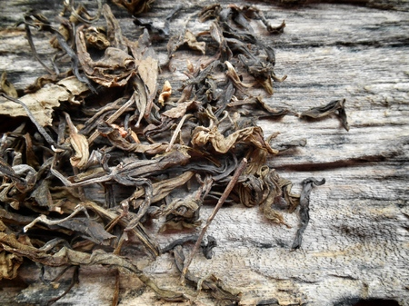Closeup of dry tea leaves on wood photo