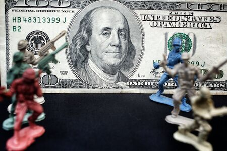 green plastic soldiers: toy soldier and weapons standing with dollar Stock Photo