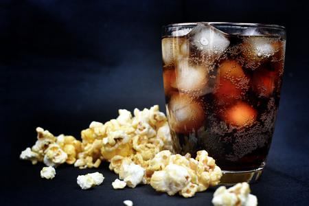 Popcorn und Cola auf dem schwarzen Hintergrund Standard-Bild