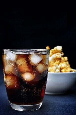 palomitas de maíz y refrescos de cola en el fondo negro