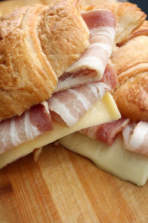 Fresh croissant with ham and cheese on rustic wooden plate photo
