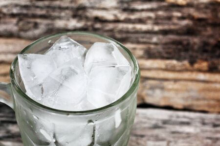 Ice cubes on the wood background photo