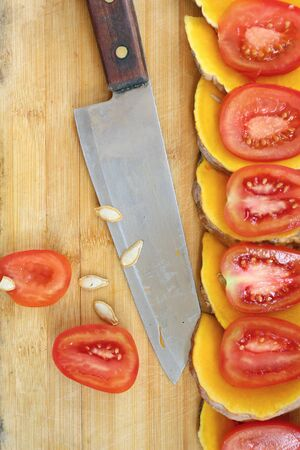 Slices of fresh pumpkins and ripe tomato photo