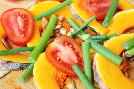 Slices of fresh pumpkins , onion flower and ripe tomato photo