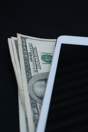 Tablet computer and dollar on black background photo