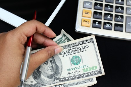Counting dollar, calculator, pen and tablet computer photo