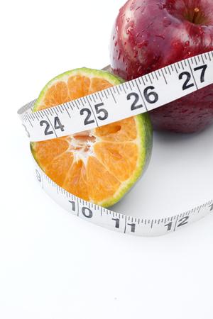 naranja fruta: cinta de la medida de frutas de naranja y manzana Foto de archivo