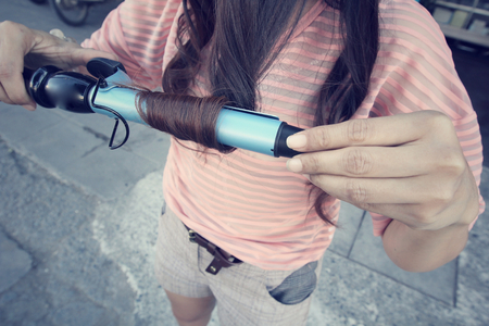 styler: Woman using straightener with hair