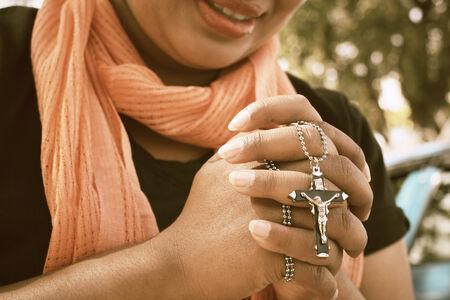 manos orando: Manos de mujer rezando con la cruz Foto de archivo