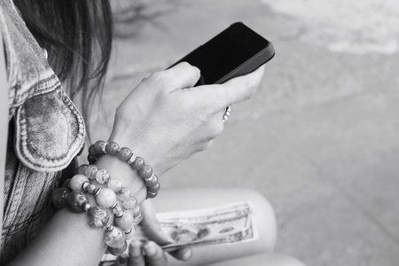 Woman using smart phone with dollar photo