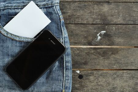 Smart phone with blank card on jeans photo