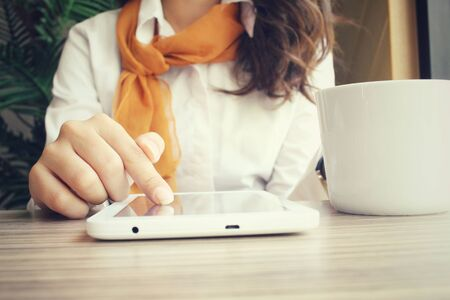 Businesswoman using tablet with drink coffee  in the cafe photo