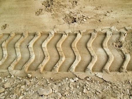 dirt: Wheel tracks on the soil.