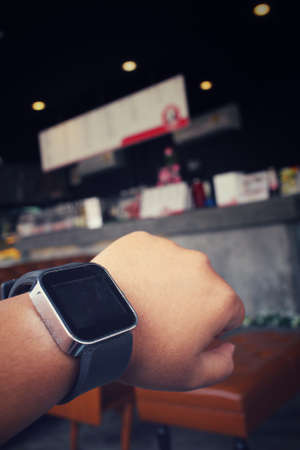 girl with a wristwatch: Woman hand with smartwatch at cafe