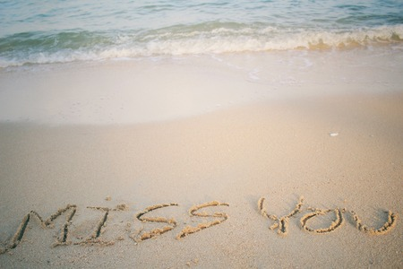 The word miss you written in sand on beach photo