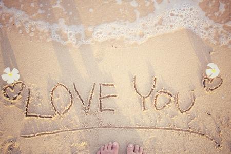 Selfie of word love you written in sand on beach photo